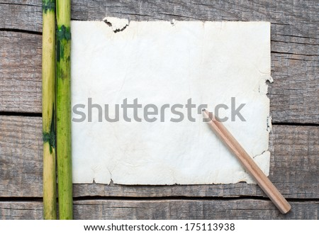 Blank paper on wooden table with bamboo and pen - stock photo