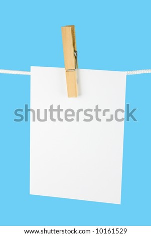 Blank paper sheet on a clothes line on blue background