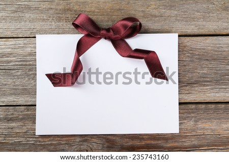 Blank paper sheet with burgundy bow on grey wooden background - stock photo