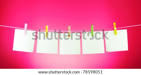 Blank paper sheets on a clothes line against the pink background