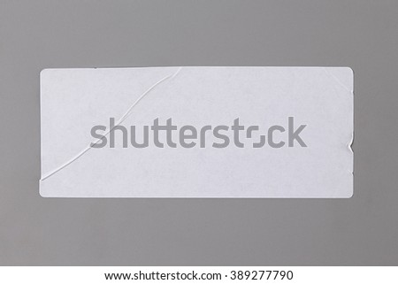 Blank Paper Tag. Label isolated on Grey Background. Sticker or Paper Adhesive with Wrinkles and Scratches. Close Up. Top View with Copy Space for Text or Image - stock photo