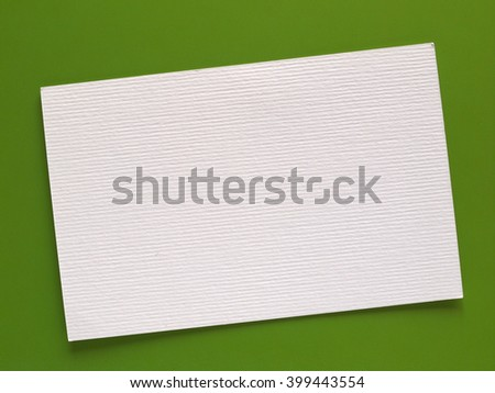 Blank paper tag label or sticker with copy space - flat lay on green desktop background - stock photo