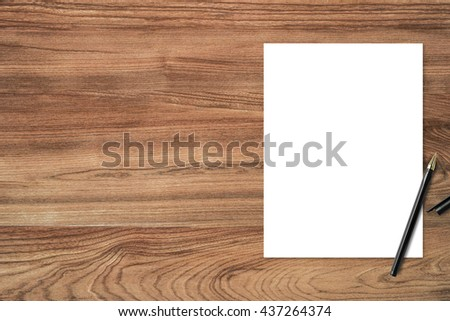 Blank paper template with pen on wooden office desk table. Top view with copy space. - stock photo
