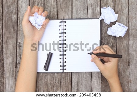 Blank paper waiting for idea with hand and pen - stock photo