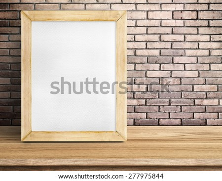 Blank paper white board on wooden table at red brick wall,Template mock up for adding your design and leave space beside frame for adding more text. - stock photo