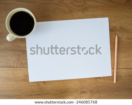 blank paper with coffee cup and pencil on wooden background