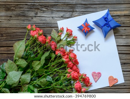 Blank paper with copy space on top of wooden surface beside bundle of roses, Valentines Day hearts, ribbons, gift box and pencil - stock photo