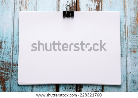 Blank paper with paper clip on wood board