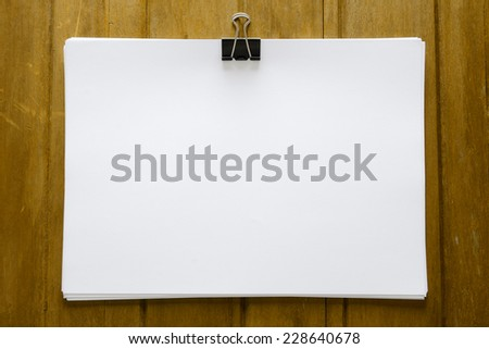 Blank paper with paper clip on wood board - stock photo