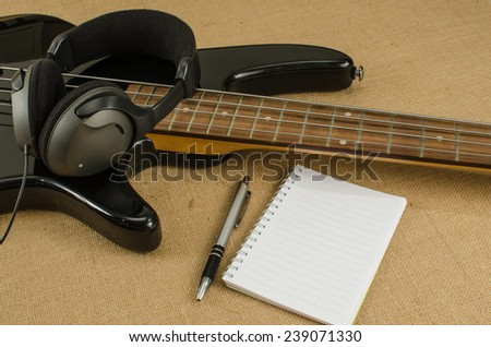 Blank paper with pen on electric bass guitar on brown sack background