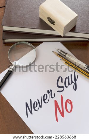 Blank paper with phrase Never say no on desk