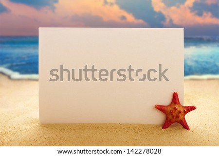 Blank paper with starfish on the sandy beach at ocean background - stock photo