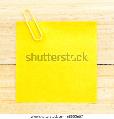 Blank paper with the clip on the wooden background