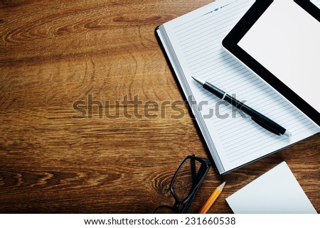 Blank Papers, Pen,Pencil, Tablet Gadget and Eyeglasses on Wooden Table with Copy Space for Texts Above. - stock photo