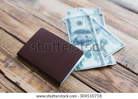 Blank passport with US dollars on wood table - stock photo