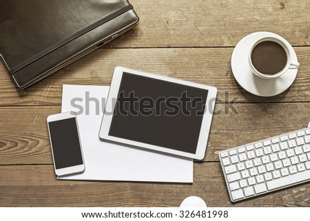 blank phone and tablet device placed over empty white paper sheets on a wooden workspace - stock photo