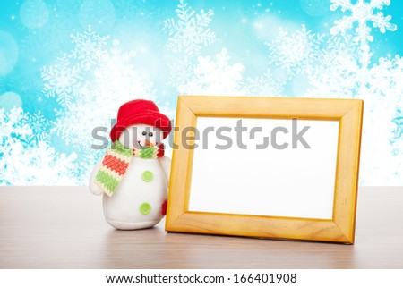 Blank photo frame and christmas snowman on wooden table over blue christmas background - stock photo
