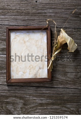 Blank photo frame and dried calla lily on wooden background - stock photo