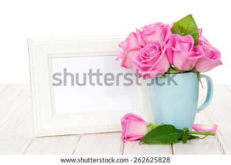 Blank photo frame and pink roses bouquet in tea cup. Over wooden table - stock photo