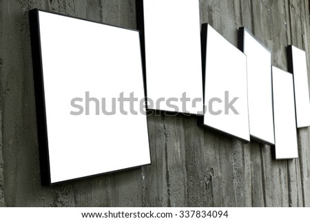 blank photo frame hanging on cement wall interior room - stock photo