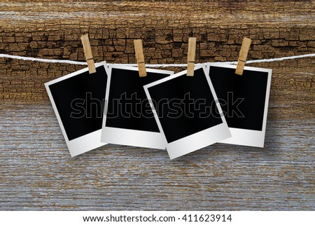 Blank photo frame with clothespin hanging on wooden background, with clipping path.