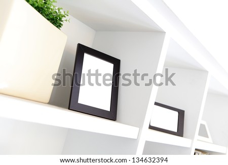 blank photo frame with copy space on white bookshelf at home - stock photo