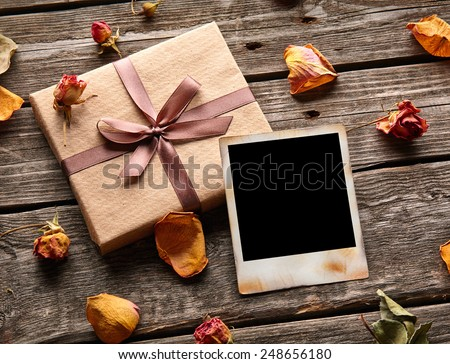 Blank photo frame with gift box, petals and rose flowers on old wooden background. - stock photo