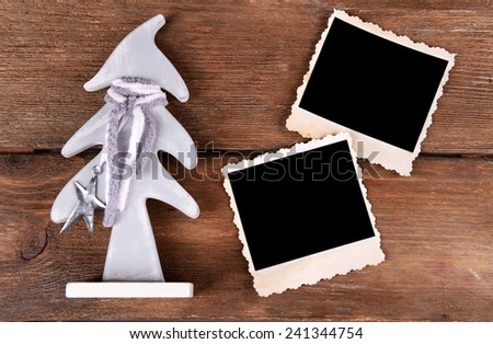 Blank photo frames and Christmas decor on wooden table background - stock photo