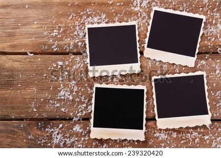 Blank photo frames and snowflakes on wooden table background - stock photo