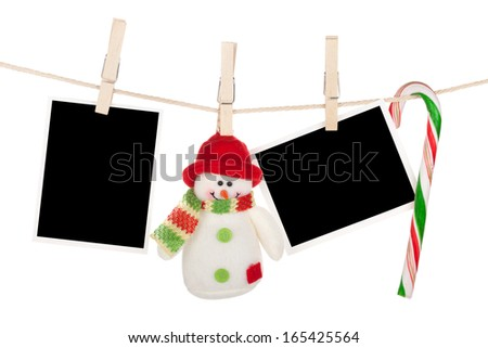 Blank photo frames and snowman hanging on the clothesline. Isolated on white background - stock photo