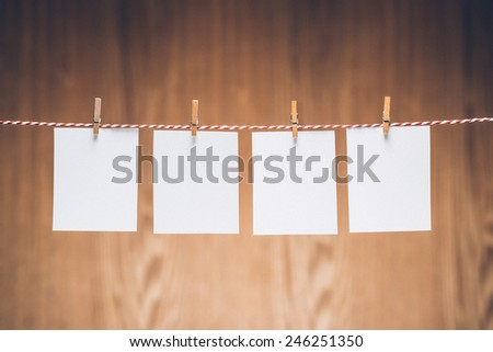 Blank photo frames hanging on the clothesline . Isolated on wooden background. Vintage style.  - stock photo