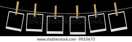 Blank photo frames on a leash. Isolated on black background. - stock photo