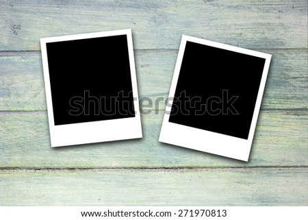 Blank photo frames on blue wood background