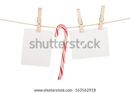 Blank photos and candy cane hanging on clothesline. Isolated on white background - stock photo