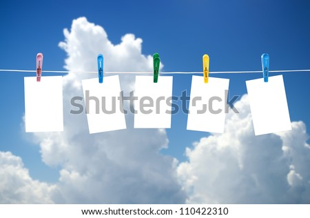 Blank photos hanging on a clothesline, blue sky on background - stock photo