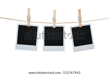 Blank photos hanging on a clothesline isolated on white background with clipping path for the inside of the frames