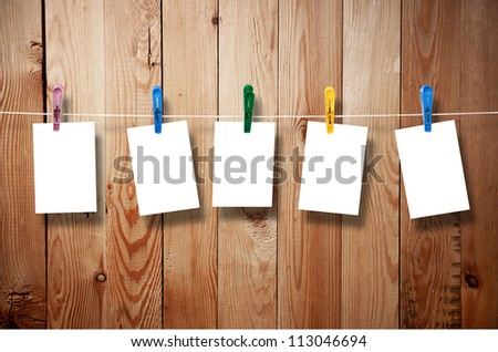 Blank picture frame hanging on clothesline on wood background - stock photo