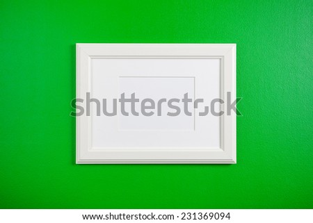 blank picture frame on a green wall  - stock photo