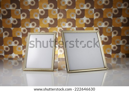 Blank picture frames against kitsch background - stock photo