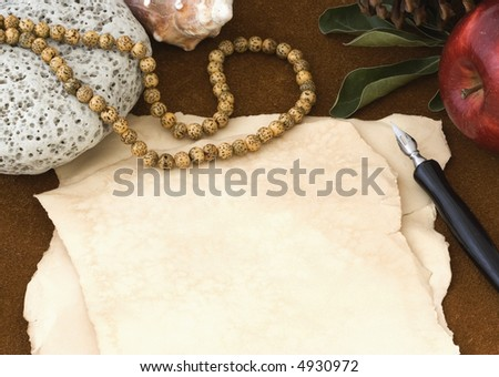 Blank piece of antiqued paper and ink pen surrounded by natural objects on brown suede background - stock photo