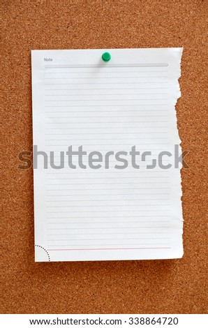 Blank piece paper pinned into brown corkboard