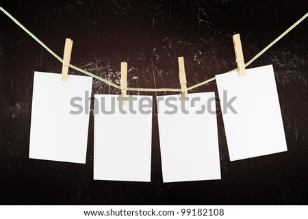 Blank pieces of paper and wooden clothespins on old wall background - stock photo