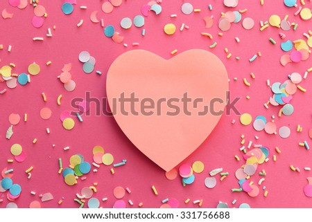 Blank pink paper note heart shape on confetti background with copy space - stock photo