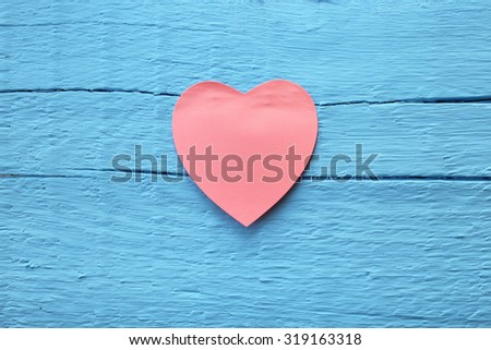 Blank pink paper note with heart shape on grunge blue wooden background with copy space - stock photo