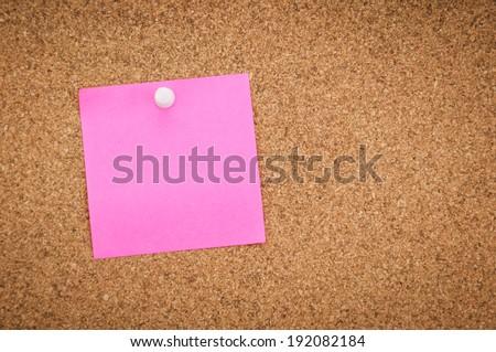 blank pink sticky note on corkboard background - stock photo