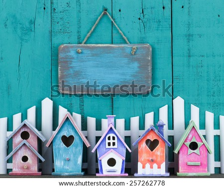 Blank pink wooden sign hanging over white picket fence and row of colorful birdhouses on antique teal blue wood background - stock photo