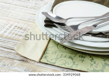 Blank plate with fork and knife on tablecloth background