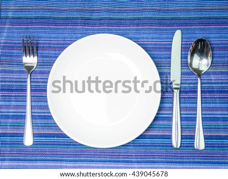Blank  plate with fork and knife on  tablecloth background - stock photo