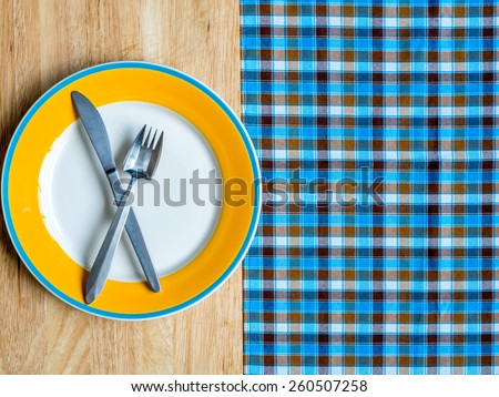 Blank plate with fork and knife on wooden table and checked tablecloth background - stock photo