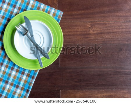 Blank plates with fork and knife on checked tablecloth over wooden table background - stock photo